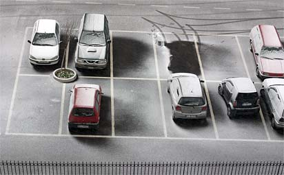 Photograph of light snow on cars in a parking lot in Formello, Italy. The view-angle is looking down from a considerable height above. Tracks of a recently departed car are evident, as is the wind direction during the snow-fall.