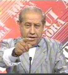 Fotografia mostrando o Luis Lopes Correa apontando o dedo para a tela durante uma ediçao do Aqui Agora, jornal televisivo onde era apresentador.