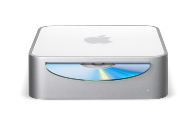 A photograph showing the Mac mini personal computer against a white background. The Mac mini's design is minimal, with only a CD slot and status light on the front.