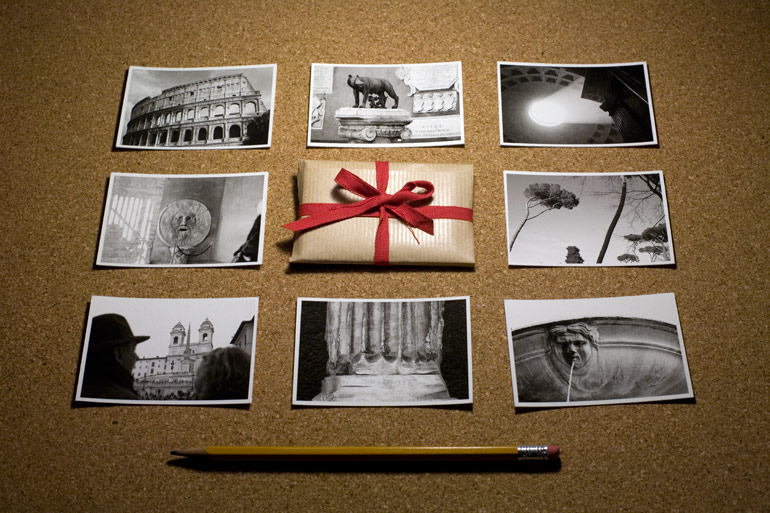A photograph of the eight prints included in the Rome print packet and the pocket print packet itself, with a pencil present for size reference.